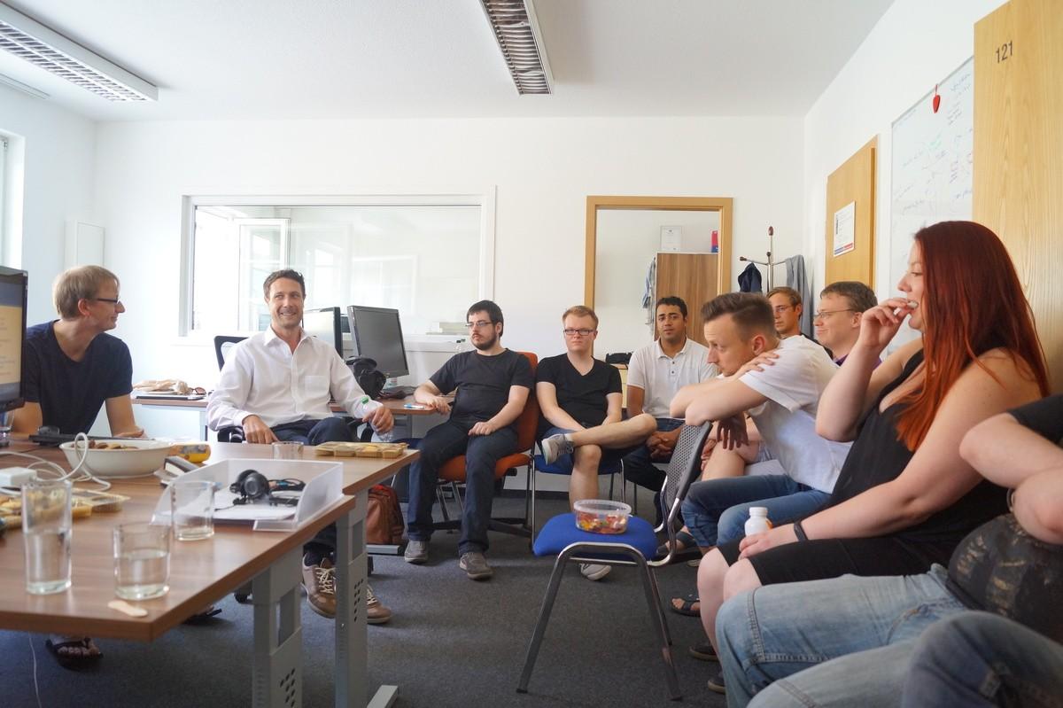 Unser Team lauscht der Präsentation von Akos Toth und Jörg Klukas zur Halbjahresreview im Büro in Dresden. (Bildquelle: pludoni GmbH)